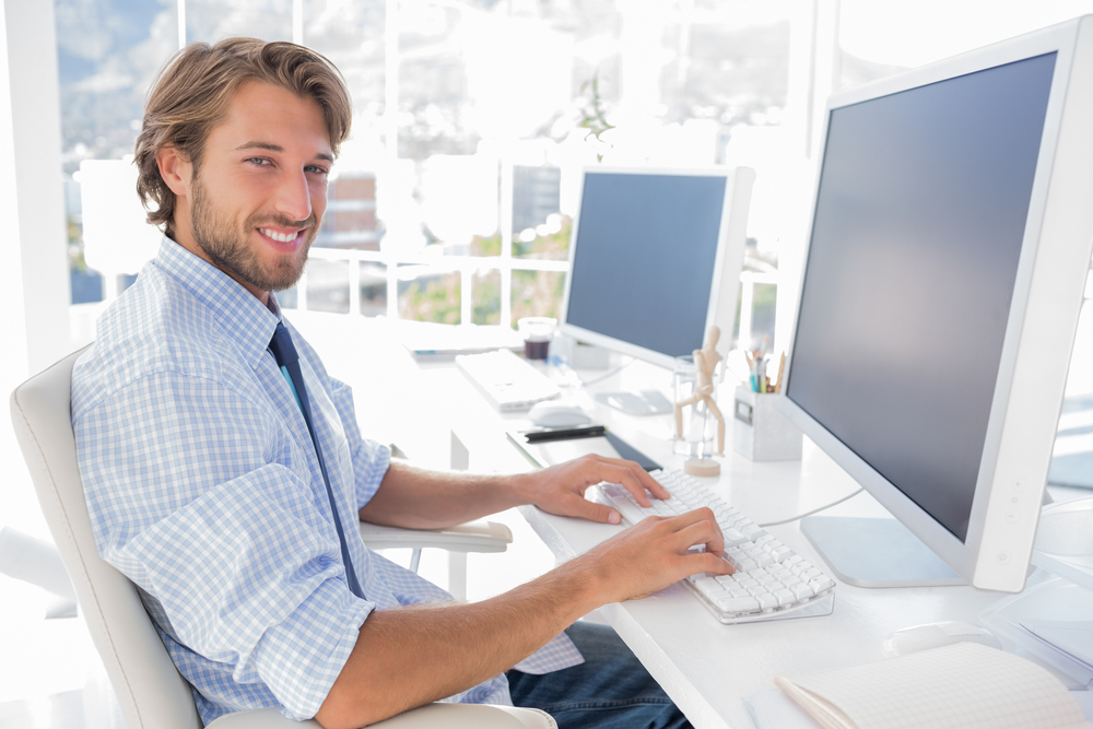 Smiling designer working at his desk in modern office